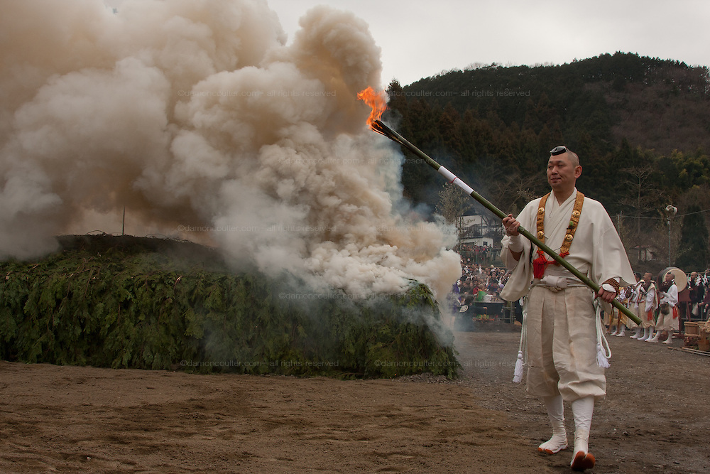 A yamabushi or mountain priest carries a torch after lighting the large bonfire of cedar branches behind him at the Hi Watari firewalking festival, Takaosan guchi near Tokyo, Japan. Sunday March 8th 2009