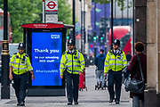 Police officers patrol practicing social distancing - Oxford street is very quiet as all the stores are shut, and signs warn people to stay home and save/thank the NHS. The 'lockdown' continues for the Coronavirus (Covid 19) outbreak in London.