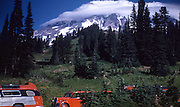 Mount Ranier as seen from Paradis Lodge, Mt. Ranier National Park, August 18, 1953. Seen in the foreground is one of the park's historic red buses which were designed for the National Parks in the 1930s and are no longer in use except for restored buses in Glacier National Park.