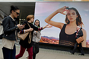 Women chatting as they walk past a billboard ad featuring the face of a model advertising a perfume outside the retailer Debenhams on Oxford Street, on 16th April 2018, in London, England.