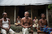 Sri Ajit Memo, 55, (centre) sits in the courtyard of his house in Ponchoki Bhajini village located inside the enclave of Dhoholakhagrabari. Being Hindu's 20 out of the 22 households, including Ajit, decided to become Indian citizen's and will move to India for ever later this year.<br /> <br /> On July 31st 2015 the enclaves that formed one of the world's most complicated borders were officially absorbed in to the countries that surrounded them in a land-mark land swap between India and Bangladesh. The people that lived in them will finally receive citizenship.<br /> <br /> Enclaves are small pockets of sovereign land completely surrounded by another sovereign nation. Approximately 160 enclaves, known as chitmahals, exist on either side of the India-Bangladesh border. For 68 years the 50,000 plus inhabitants of these enclaves have lived a difficult existence, stranded from their home nation and ignored by the country that surrounds them. <br /> <br /> In theory even leaving their enclaves is illegally crossing an international border and for decades it has been very difficult for them to receive even the most basic of rights whether education or health. Even the police have no jurisdiction in the enclaves leaving them essentially lawless.