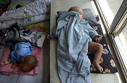 KABUL,AFGHANISTAN - AUGUST 29: Amir Rahman, 2, and Farshad, 6 months, sleep in the Indira Ghandi Hospital for Children August 29, 2002 in Kabul Afghanistan. The hospital has 300 beds but usually it is filled at double capacity with only 118 doctors. One in four children die before the age of 5 in Afghanistan. (Photo by Ami Vitale/Getty Images)