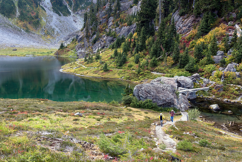 Two hikers make their way up the Chain Lakes Trail to the Heather Meadows parking lot.  Photographed from the Bagley Lakes/Heather Meadows area of the Mount Baker-Snoqualmie National Forest in Washington State, USA.