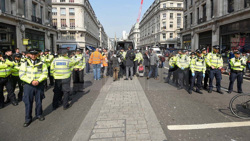 """© Licensed to London News Pictures. 17/04/2019. LONDON, UK.  Police officers gathered at Oxford Circus during """"London: International Rebellion"""", on day three of a protest organised by Extinction Rebellion, demanding that governments take action against climate change.  Marble Arch, Oxford Circus, Piccadilly Circus, Waterloo Bridge and Parliament Square have been blocked by activists in the last three days.  Police have issued a section 14 order requiring protesters to convene at Marble Arch only so that the protest can continue.  Photo credit: Stephen Chung/LNP"""