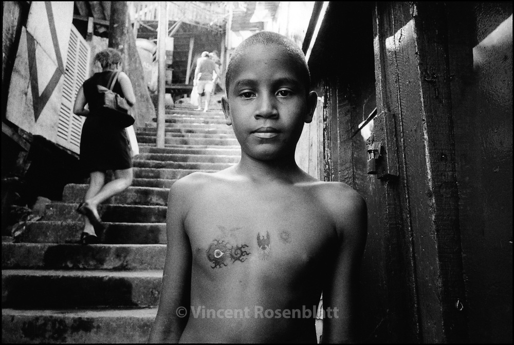 "A child from favela Santa Marta proudly shows his fake tattoos.. ||.Um menino na favela Santa Marta mostra com orgulho as suas ""tatuagens""."