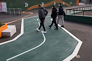 Three youths cross a new cycling path, a regenerated landscape created outside Croydon College and Fairfield Hall, on 20th January 2020, in Croydon, London, England.