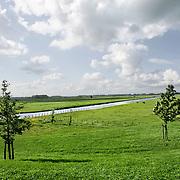 Nederland Bergambacht 29 mei 2006 20060529 Foto: David Rozing .Groene hart, pal naast het gemaal Krimpenerwaard en watergang ligt een woning in een polderlandschap. Een gemaal is een inrichting om water van een lager naar een hoger niveau te brengen. Het brengt of houdt water in een peilgebied op een bepaald peil. ..Serie tbv Schieland en de Krimpenerwaard, deze zorgt als waterschap voor droge voeten en schoon water in een bepaald gebied. Het beheersgebied van Schieland en de Krimpenerwaard strekt zich uit tussen Rotterdam, Schoonhoven en Zoetermeer. Binnen dit gebied zorgt Schieland en de Krimpenerwaard voor de kwaliteit van het oppervlaktewater, het waterpeil en de waterkeringen. Daarnaast beheert Schieland en de Krimpenerwaard een aantal wegen in de Krimpenerwaard...Foto David Rozing