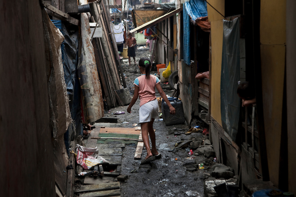 A girl walks between shack.s Slum area in Tondo, Manila, Philippines