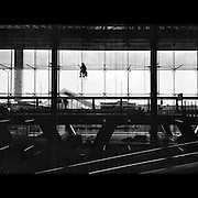 A window Cleaner hangs from the roof as he cleans the front windows of Suvarnabhumi Airport, also known as Bangkok International Airport