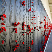 Wall commemorating those who have died in military service of Australia. The red poppies are a traditional tribute. Australian War Memorial in Canberra, ACT, Australia