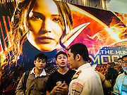 20 NOVEMBER 2014 - BANGKOK, THAILAND: A movie theater security guard confronts Thai students who tried to make a statement before the new Hunger Games movie in Bangkok. At least three people were arrested by Thai police during the opening the Hunger Games: Mockingjay - Part 1 in Bangkok Thursday. Opponents of the Thai military coup have adapted the three fingered salute used in the Hunger Games series as a sign of their opposition to the coup. In the weeks before the movie opening Thai police arrested several people for using the Hunger Games salute and Thai media reported that one Thai movie theater chain cancelled plans to show the movie at the request of the military government. There were several small protests at theaters showing the movie Thursday.     PHOTO BY JACK KURTZ