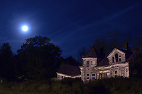 A full moon hovers over an abandoned house in Searsport, Maine.