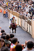 A horse gets a run-up before climbing the hill at the annual Shinto Tado Horse Festival.