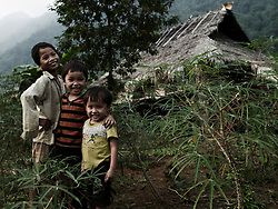 Three little ethnic boys stand in a line in front of a small house with smiles on their faces for the camera. Pu Luong area, Hoa Binh Province, Vietnam, Southeast Asia