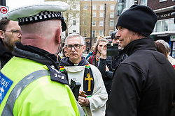 London, UK. 16th April 2019. A priest who had been officiating at a church service in Edgware Road placates a police officer who had been trying to obtain identification details from an Extinction Rebellion campaigner during the second day of International Rebellion UK activities by climate campaigners from Extinction Rebellion to call on the Government to take urgent action to address climate change.