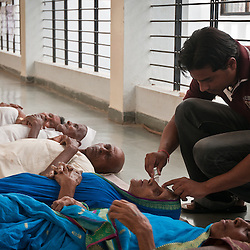 Patients are prepped for cataract surgery while laying on the ground outside of the operating room.