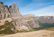 "From Piegan Pass, hikers descend Cataract Creek Valley beneath the pinnacle of Mount Gould in the Lewis Range, in Glacier National Park, Montana, USA. A scenic walking traverse starts from Siyeh Bend over Piegan Pass to Many Glacier, visiting glorious mountains, valleys and lakes over 13 miles (2260 feet up, 3520 feet down). Since 1932, Canada and USA have shared Waterton-Glacier International Peace Park, which UNESCO declared a World Heritage Site (1995) containing two Biosphere Reserves (1976). Rocks in the park are primarily sedimentary layers deposited in shallow seas over 1.6 billion to 800 million years ago. During the tectonic formation of the Rocky Mountains 170 million years ago, the Lewis Overthrust displaced these old rocks over newer Cretaceous age rocks. Glaciers carved spectacular U-shaped valleys and pyramidal peaks as recently as the Last Glacial Maximum (the last ""Ice Age"" 25,000 to 13,000 years ago). Of the 150 glaciers existing in the mid 1800s, only 25 active glaciers remain in the park as of 2010, and all may disappear by 2020, say climate scientists."