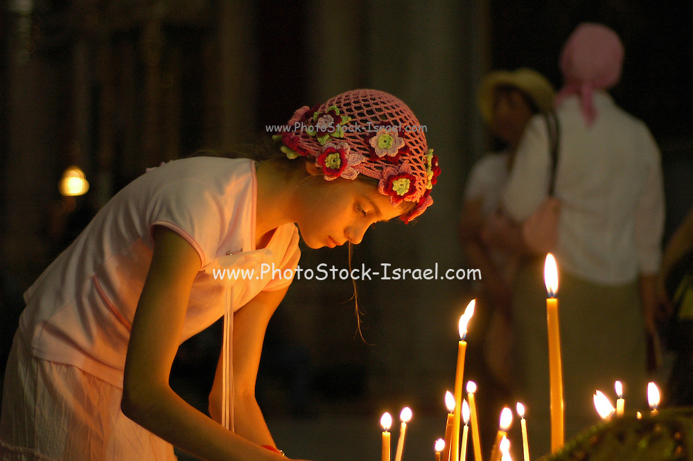 Church of the Holy Sepulchre, in the Christian quarters, Jerusalem, Israel, Easter 2006, young girl lighting candles