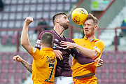 David Vanecek (#32) of Heart of Midlothian FC jumps between Keaghan Jacobs (#7) of Livingston FC and Alan Lithgow (#4) of Livingston FC during the 4th round of the William Hill Scottish Cup match between Heart of Midlothian and Livingston at Tynecastle Stadium, Edinburgh, Scotland on 20 January 2019.