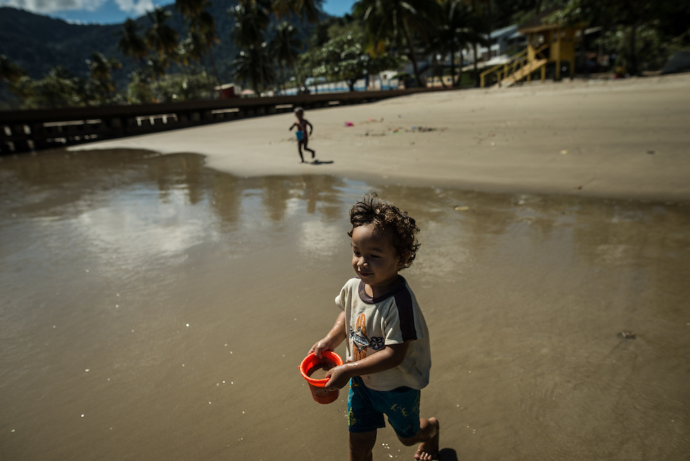 MARACAS BAY, TRINIDAD - FEBRUARY 14, 2017: Lucah Chin, 2, plays on the beach filling buckets with sand and water at Maracas Bay, the most popular beach within reach of the capital where crowds of people flock to go swimming in the clean, warm sea backed by lush green hills.  PHOTO: Meridith Kohut for The New York Times