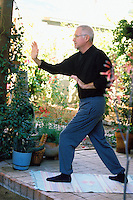 A mature man practicing his Tai Chi routine on his back patio.