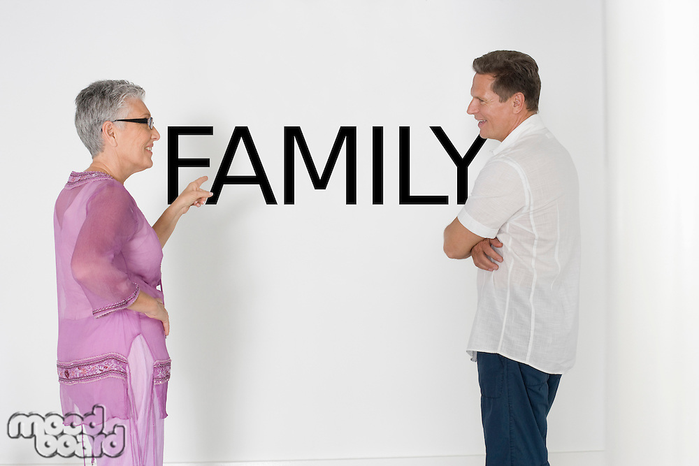 Couple discussing family issues against white wall with English text