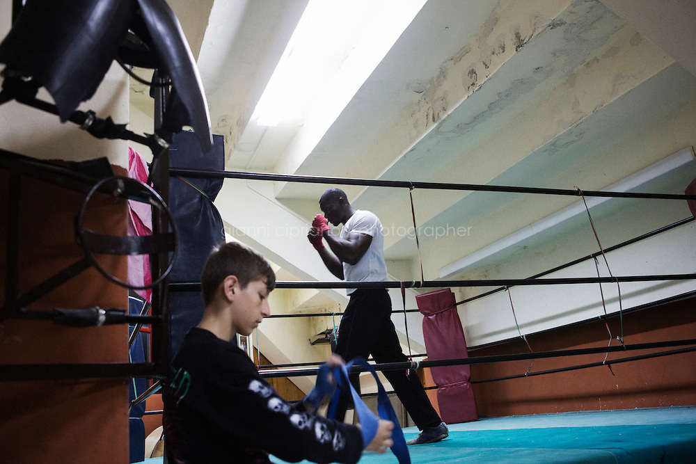 RAMACCA, ITALY - 26 NOVEMBER 2014: Francis Ibizugne, a 25 years old asylum seeker from Nigeria, trains as a boxer in a gym in Ramacca, Italy, on November 26th 2014.<br /> <br /> Francis lives at the  the CARA (Accommodation Centre for Asylum Seekers) of Mineo, where approximaley 4,000 asylum seekers live. Francis was rescued on a boat carrying 750 asylum seekers from Ghana, Gambia, Nigeria, Syria and Pakistan on April 9th, 2014, after 11 hours in the Mediterranean Sea. He left Nigeria in 2009, then lived and worked in Libya for 13 months as a mechanic. He left Libya after his safety was theathened and was shot in a leg.<br /> <br /> By law, asylum-seekers can be held for 35 days in a CARA. In reality, the average stay is closer to a year.The Cara is located at the &quot;Residence degli Aranci&quot; (Residence of the Oranges), a small town built to accomodate the families of US soldiers operating at the Naval Air Station of Sigonella 40km away. Since 2011 the &quot;Residence degli Aranci&quot; hosts the Accommodation Center for Asylum Seekers, which has since then hosted more than 12,000 seekers of 47 nationalities and over 200 ethnic groups. The CARA of Mineo includes 404 houses. Each housts from 7 to 11 asylum seekers.