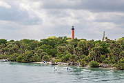Paddle boarders travel along the Indian River past the Jupiter Inlet Lighthouse at the South Beach Bridge in Jupiter, Florida.