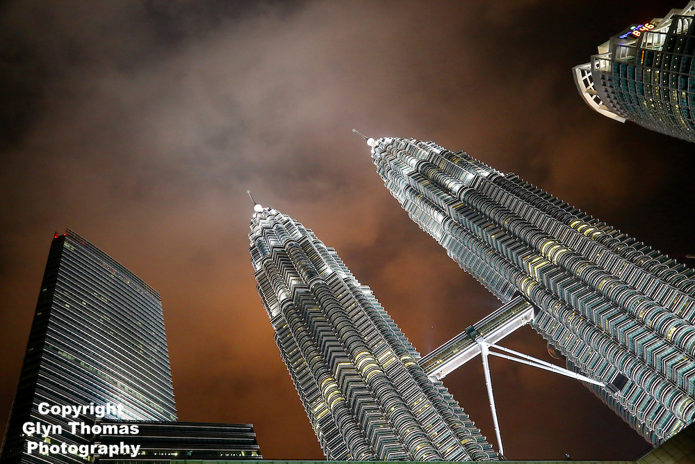 Petronas Towers in Kuala Lumpur with a stormy sky behind at sunset, Malaysia