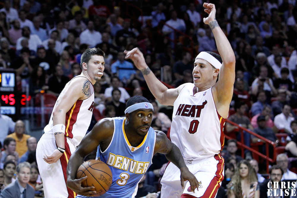 19 March 2011: Denver Nuggets point guard Ty Lawson (3) drives past Miami Heat point guard Mike Bibby (0) during the Miami Heat 103-98 victory over the Denver Nuggets at the AmericanAirlines Arena, Miami, Florida, USA.