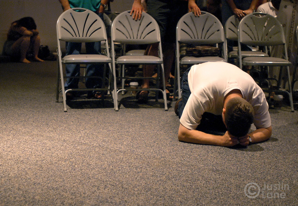 A man bows in prayer during a Saturday evening service at New Life Church in Colorado Springs, CO on July 9, 2005. The church has 11,000 members and is led by pastor Ted Haggard.