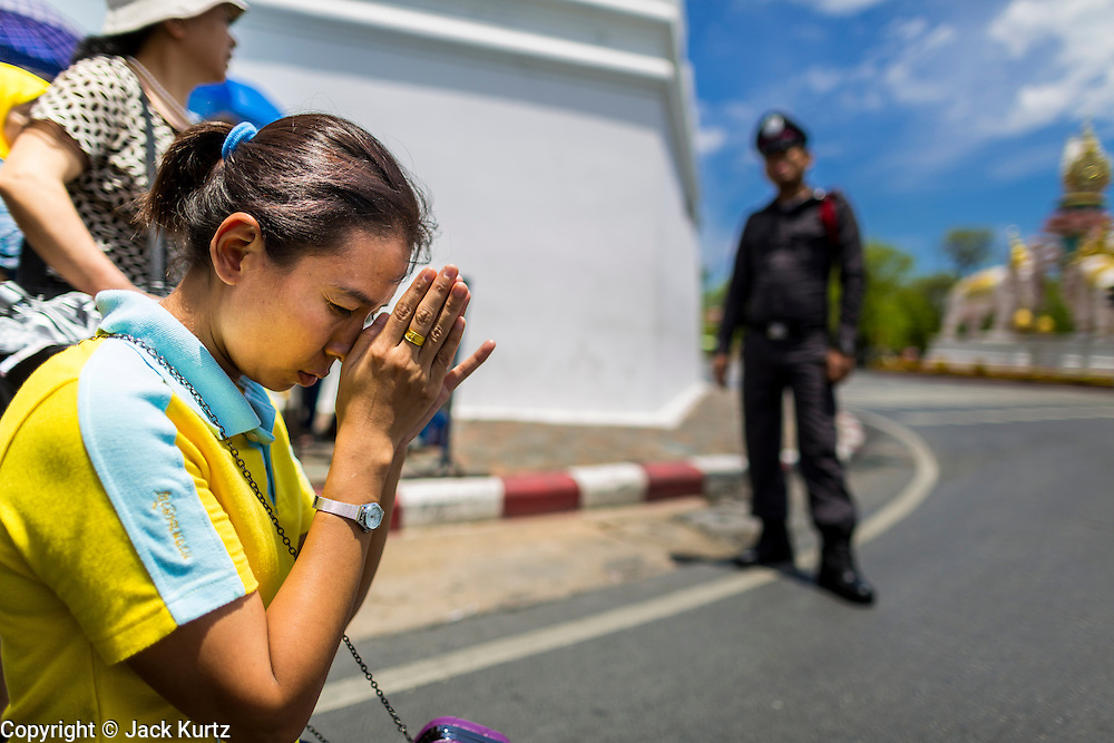 "05 MAY 2013 - BANGKOK, THAILAND:   A woman prays in the street after waiting to Bhumibol Adulyadej, the King of Thailand, Sunday. The King and Queen, who are both hospitalized and in poor health, did not attend Sunday's event. May 5 marks the 63rd anniversary of the Coronation of His Majesty King Bhumibol Adulyadej. The day is celebrated as a national holiday; since this year it falls on a Sunday, it will be observed on Monday May 6, and as such all government offices and commercial banks will close for the day. HM King Bhumibol Adulyadej is the longest reigning monarch in the world. Each year on the 5th of May, the Kingdom of Thailand commemorates the day when, in 1950, the Coronation Ceremony was held for His Majesty King Bhumibol Adulyadej, the 9th in the Chakri Dynasty (Rama IX). On the 5th of May, His Majesty conducts a merit making ceremony, presenting offerings to Buddhist monks, and leads a ""Wien Thien"" ceremony, walking three times around sacred grounds at the Temple of the Emerald Buddha.    PHOTO BY JACK KURTZ"