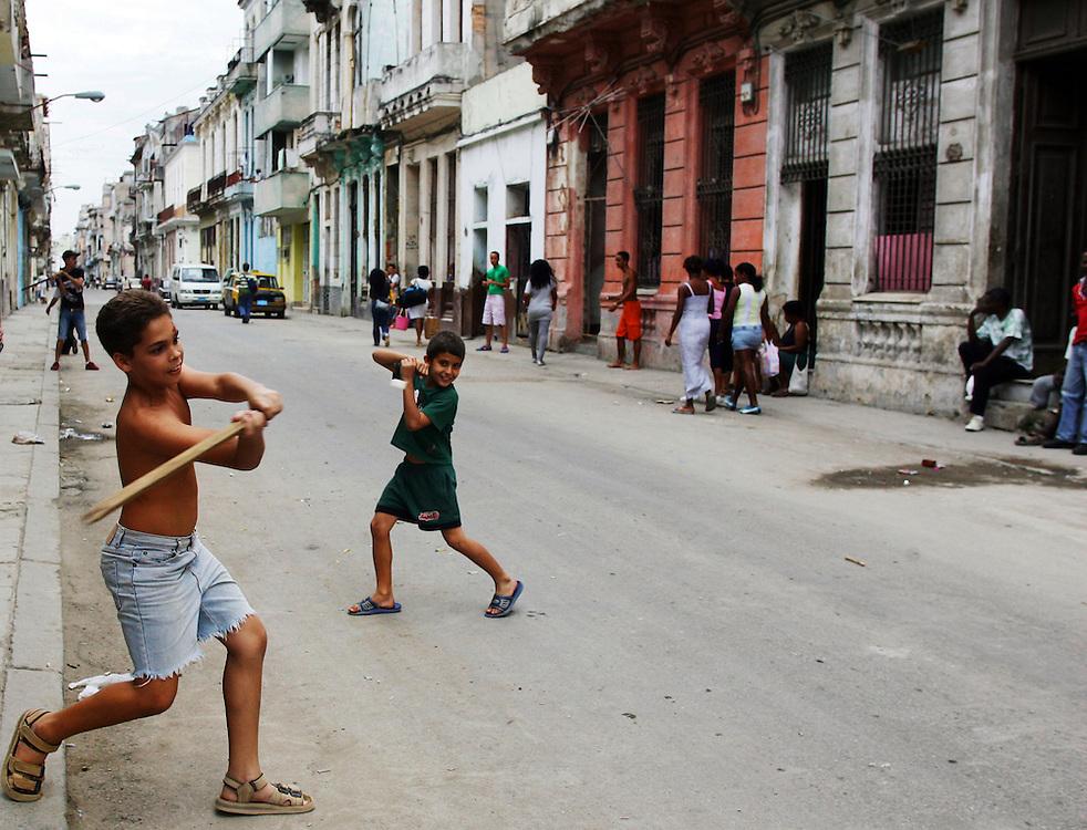 kids play baseball in a typical street scene in Havana , Cuba.