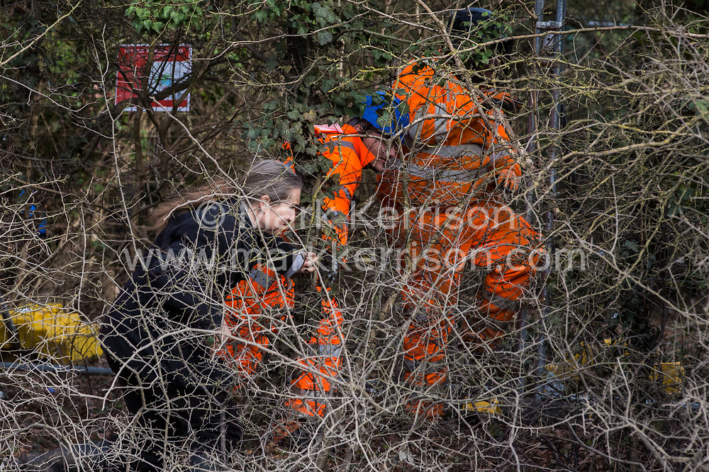 Harefield, UK. 8 February, 2020. Environmental activists seek to prevent HS2 engineers from using a chainsaw to carry out tree felling works for the high-speed rail project alongside Harvil Road in the Colne Valley. The activists, based at a series of wildlife protection camps in the area, prevented the tree felling, for which road and rail closures had been implemented, for the duration of the weekend for which it had been scheduled.