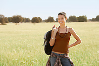Female hiker holding backpack standing in field portrait