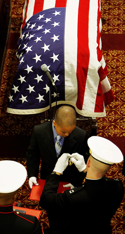 Tristan Whyte (C), 10, is pinned by a U.S. Marine with the Purple Heart medal for his brother, United States Marine Lance Cpl. Nicholas J. Whyte, in front of his casket during his funeral at the Bedford Central Presbyterian Church in Brooklyn, New York on Friday 30 June 2006. Whyte was killed on 21 June 2006 while serving in Iraq.