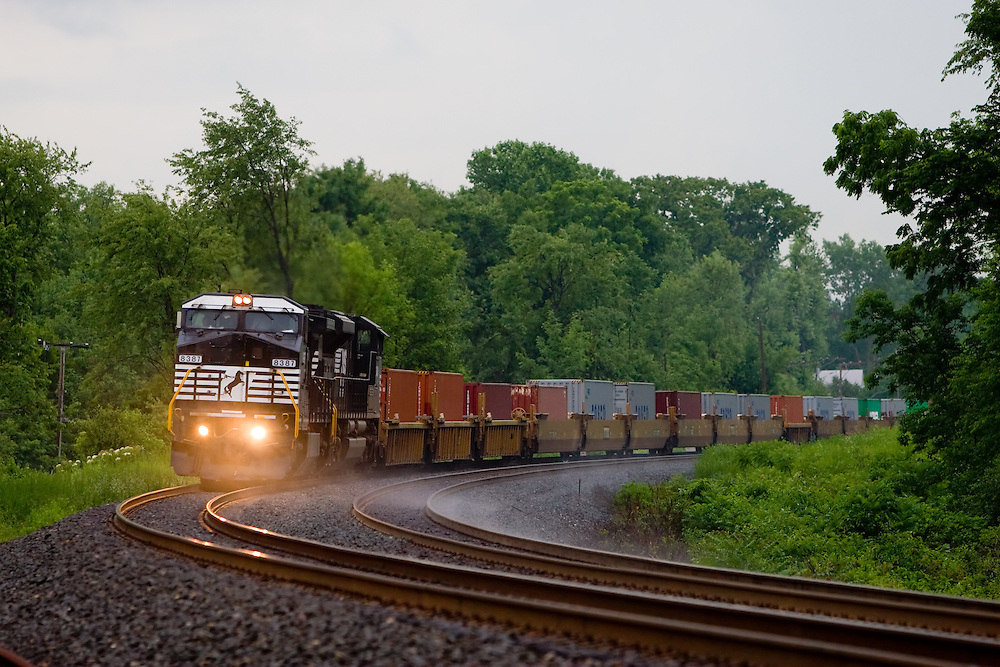 After a torrential downpour during a typical Midwestern summer thunderstorm, a westbound Norfolk Southern intermodal train swings around the big curve in Otis, IN.