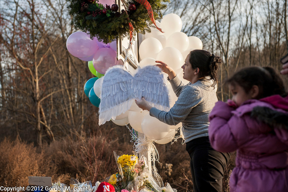 Newtown, CT - 12/15/12 -  Judith DeLisa places the wings of her daughter, Calliope Ceballos, 5, right, on a memorial site near the Sandy Hook Elementary School in Newtown, CT Saturday afternoon, to remember the victims of the school shooting in Newtown, CT December 15, 2012.    (Photo by Gordon M. Grant)