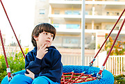 Day dreaming young boy looks forward to the future in a playground