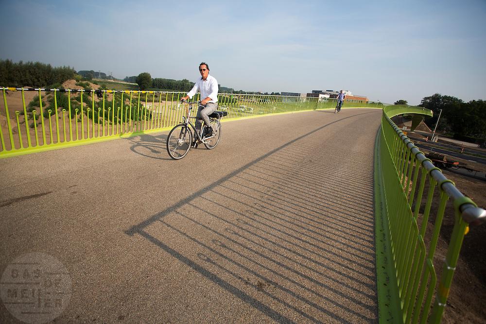 Bij Lent rijden fietsers over 't Groentje, de nieuwe fietsbrug die onderdeel is van het Rijn-Waalpad, de snelfietsroute tussen Arnhem en Nijmegen. Als de route helemaal klaar is, kunnen fietsers binnen 40 minuten van Arnhem naar Nijmegen fietsen. De snelfietsroute kent weinig obstakels en moet het aantrekkelijk maken om ook langere afstanden met de fiets af te leggen.<br /> <br /> Cyclists ride on 't Groentje (the little green), the new bike bridge which is part of the Rijn-Waalpad, the fast cycling route between Arnhem and Nijmegen. When the route is finished, cyclists can get within 40 minutes from Arnhem to Nijmegen. The fast cycle route has few obstacles and to make it attractive to commute long distances by bicycle.