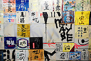 A wall is plastered with sake bottle labels in Nonbeiyokjocho, or Drunkard's Alley, in trendy Shibuya district, Tokyo. Nonbeiyokocho began life immediately after World War II as a group of tea houses. Though the alley is just a short walk from the central Shibuya shopping district, the rents are low due to the area being built over a river. Today 47 eateries, each with barely enough room to swing a cat, serve beer, fine wines and good, inexpensive fare.