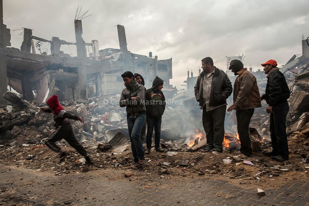 """Shejaya, quartiere a nord della striscia di Gaza. Una delle zone piu colpite dall'attacco israeliano """"Margine protettivo"""". Il quartiere è stato raso al suolo. La popolazione, a distanza di sei mesi dalla fine della guerra, vive tra le macerie della propria casa, al freddo, senza luce, gas e acqua. Nella foto uomini bruciano materiali per riscaldarsi in mezzo alle macerie delle case completamente distrutte."""