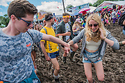 Couples help each other as people take a short cut through the mud as it begins to dry - The 2016 Glastonbury Festival, Worthy Farm, Glastonbury.