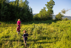 A woman and her two young sons walk in a field in Duxbury, Vermont.