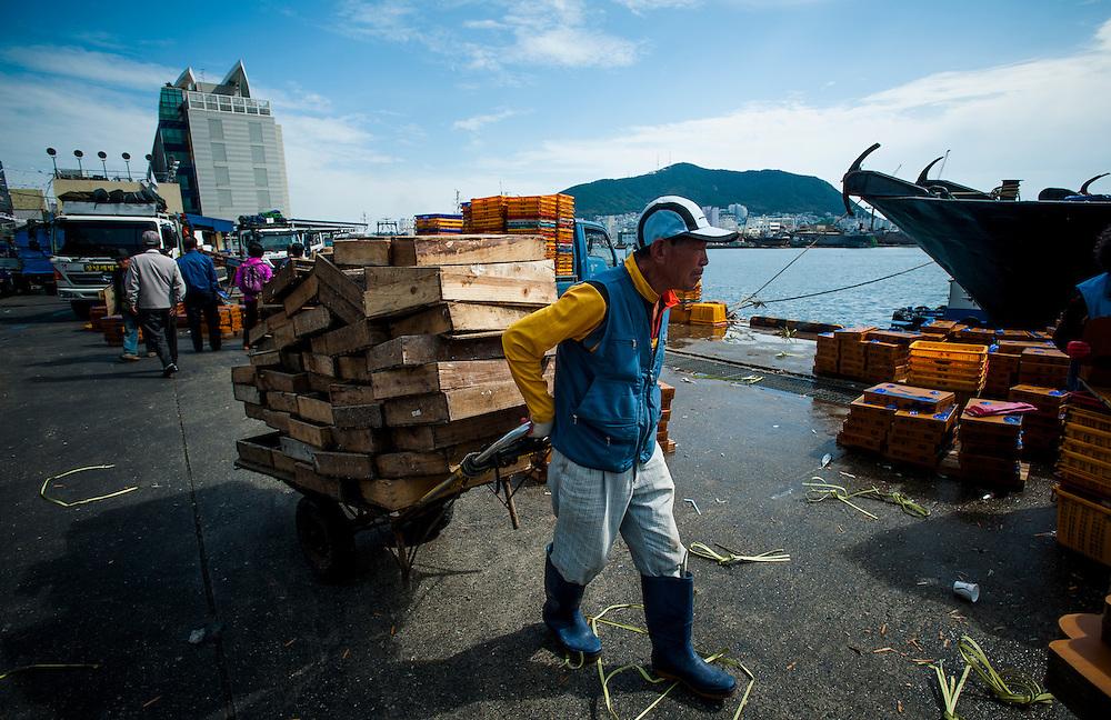 A vendor moving empty seafood crates at Jagalchi Market, Busan, South Korea, October 13, 2012.