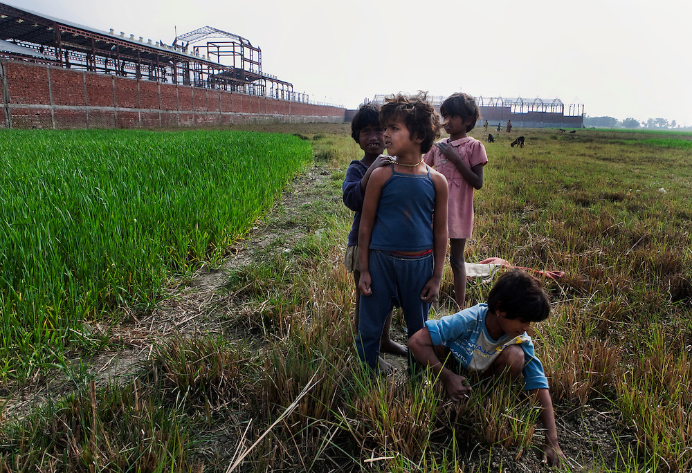 Village children play in the recently cut wheat fields growing adjacent to the boundary walls of the semi constructed asbestos factory of Balmukund Cement and Roofings Ltd. (BCRL) , Chainpur, Muzzafarpur Dist. Bihar, India, on Thursday, February 17, 2011. Photographer: Prashanth Vishwanathan/Bloomberg News
