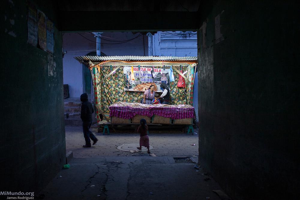 Locals walk in an alley in Santa Maria Chiquimula, Totonicapan, Guatemala. October 25, 2014.