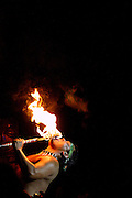 A dancer places a flaming torch onto his tongue during a traditional luau performance in Maui, Hawaii.