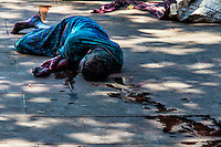 Trail of Misery: A trail of water leads one to a poor man laying face down on the concrete, Kolkata (Calcutta )India.