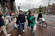 Een man op de fiets en voetgangers passeren een bouwplaats aan het Rokin in Amsterdam.<br /> <br /> Pedestrians and a cyclist pass a construction area at the Rokin in Amsterdam.